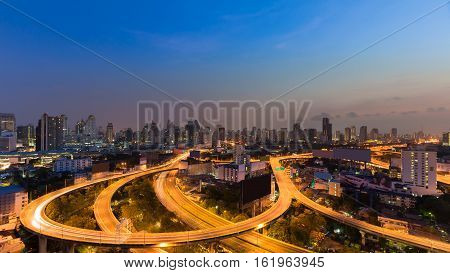 Highway interchanged curved with city downtown background, long exposure