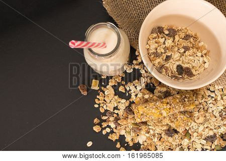 Bowl Of Muesli With Dry Fruits And Bottle Of Plant Milk, On Black Background.
