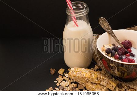 Bowl Of Muesli With Frozen Berries And Bottle Of Plant Milk, On Black Background.