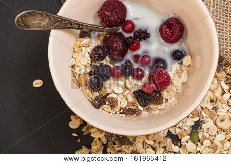 Bowl Of Muesli With Frozen Berries And Plant Milk, On Black Background.