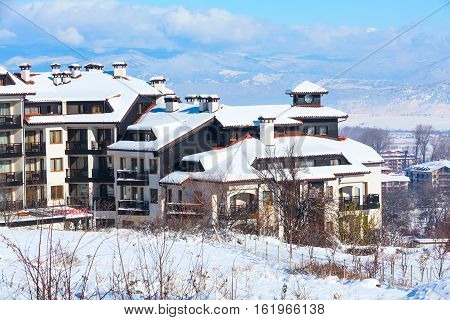 Bansko, Bulgaria - November 30, 2016: Wooden chalet, houses and snow mountains landscape panorama in bulgarian ski resort Bansko, Bulgaria