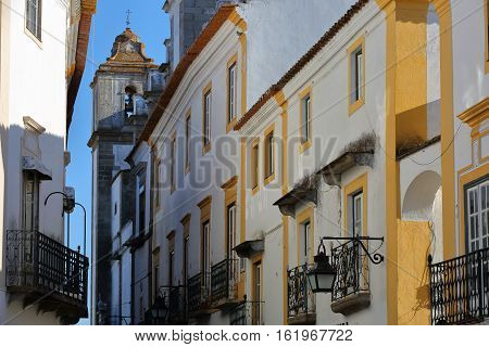 EVORA, PORTUGAL:  typical narrow street with houses painted in white and yellow and Santo Antao church in the background