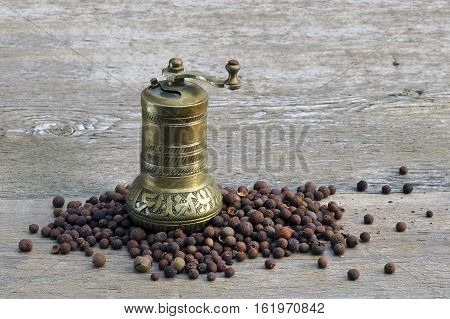 Pepper and copper pepper mill on a wooden table