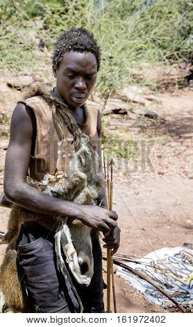 AFRICA, TANZANIA, MAY, 10, 2016 -Hazabe bushman of the hadza tribe dressed in skins baboon with arrows in the hands for hunting. Hadzabe tribe threatened by extinction in Tanzania, Africa Hadzabe tribe threatened by extinction in Tanzania, Africa
