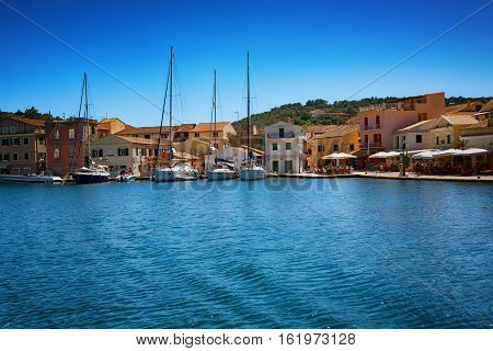 The Island of Paxos, Greece, 22 May, 2016: Early summer of the Island of Paxos - The Port of the Island of Paxos with buldings and boats around it.