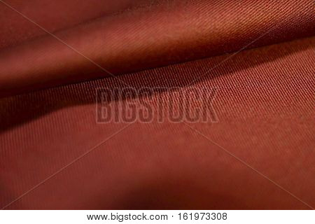 close up roll auburn fabric of suit photo shoot by depth of field for object