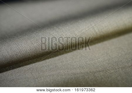 close up roll texture brown gold fabric of suit photo shoot by depth of field for object
