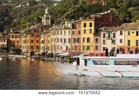 PORTOFINO ITALY - DECEMBER 9 2016: Tourists on a ferry photographing the ancient village of Portofino with the colorful houses. Genova Liguria Italy
