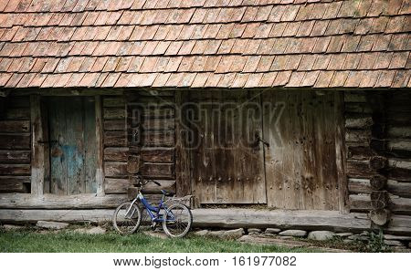 Old blue bicycle near wood shed with tale roof.