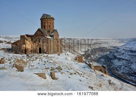 Ruins of famous Saint Gregory (Tigran Honents) church is surrounded with winter landscape. Ani is a ruined medieval Armenian city-site situated in the Turkish province of Kars near the border with Armenia.