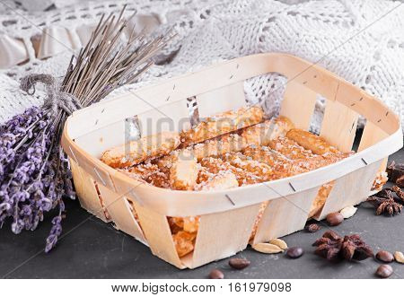 a sugar homemade biscuits piled in a wicker basket on a dark background with lace knitted blanket in the background haze filter