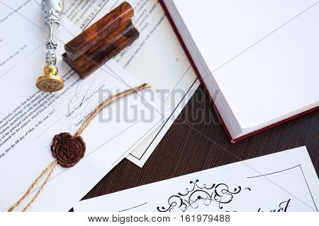 Wax seal, stamp and documents on table