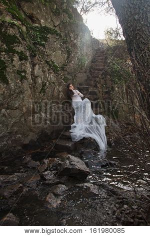 Young woman with blue eyes dressed bride sitting on a stone stairs in the countryside near a river just before marriage.