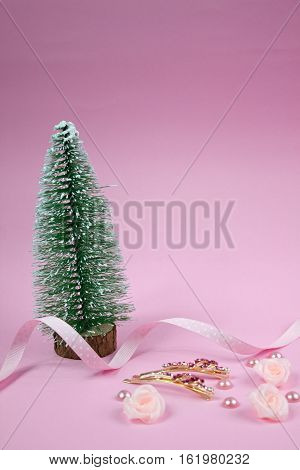 Christmas tree with Golden hairpins with pink gemstone,pink textile roses, polka dot ribbon on pink background