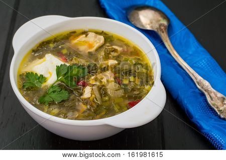 Green soup with sorrel, parsley and sour cream. Wooden blackbackground. Top view. Close-up