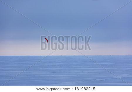kiteboarding kajtserfingom rides at sunset on the frozen Finnish Gulf sports sea skyline winter snow ice Saint Petersburg Russia