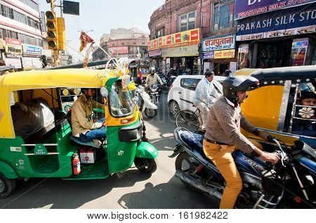 JAIPUR, INDIA - JAN 22, 2015: Bikes yellow-green rickshaw cabs and cars on the street traffic jam in big indian city on January 22, 2015. Jaipur with population 6664000 people is a capital of Rajasthan