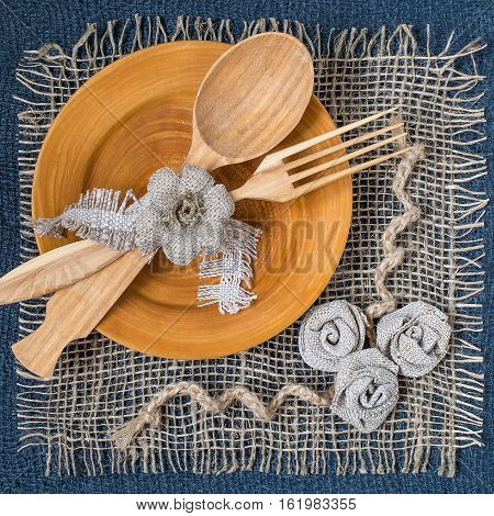 Burlap eco-friendly decor. DIY concept. Homemade napkin of burlap with handmade flowers for the table. Wooden plate spoon fork on napkin of burlap. Vintage rustic style. Square image