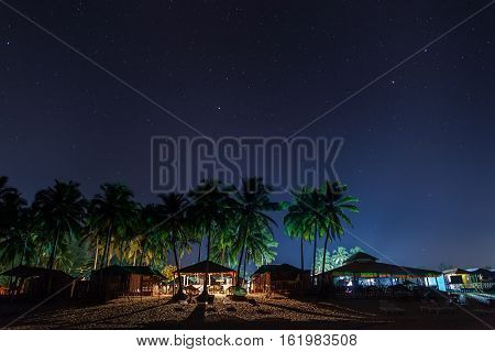 Coastal cafes restaurants and beach lodges in night illumination under the star sky between the palms.
