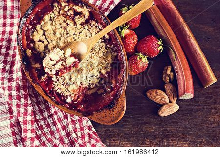 pie crumble with strawberries and rhubarb on wooden table