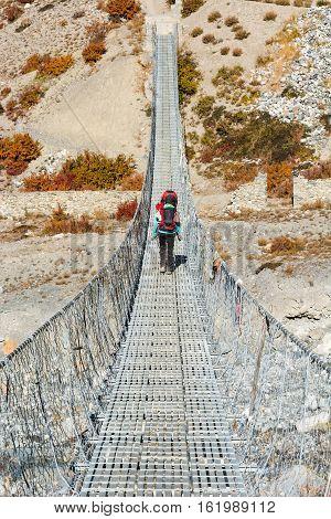 Trekker crossing metal suspension bridge. Hiking in Nepal.