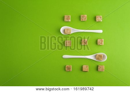 Brown sugar cubes and white teaspoons on greenery background arringed in rows. Top view. Flat lay. Copy space for text. Diet unhealty sweet addiction concept
