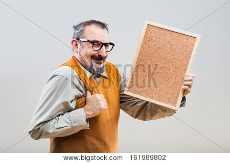 Excited nerdy businessman is holding empty cork board.