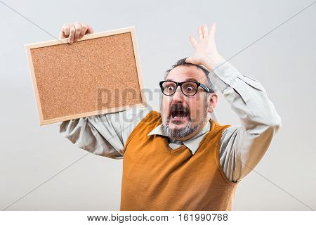 Nerdy businessman is in panic because of something while holding empty cork board.