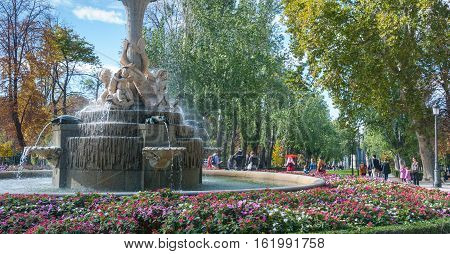 Madrid, Spain - November 9th, 2013:    Tourism in Spain.  A fountain is well attended in Retiro Park.   Human Marionette doll entertains a crowd.  People take advantage of beautiful weather conditions in The Park of Madrid in the city's core.
