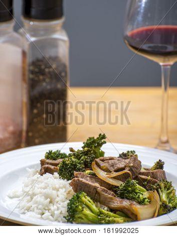 Cooked beef and broccoli stirfry served on rice with a wine glass and spices in the background