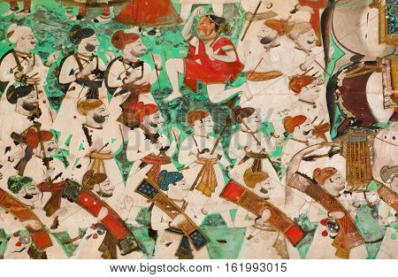 Many soldiers with guns go in orderly rows walk on a fresco of Indian palace in Rajasthan, India. 17th century fresco of Bundi Palace it is situated on hill adjacent to Taragarh Fort