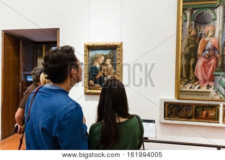 Tourists View Painting In Room Of Uffizi Gallery