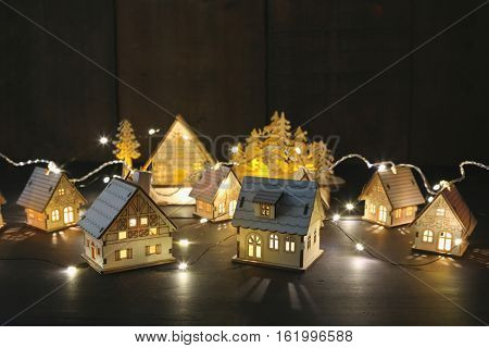 Small wooden houses with lights on table