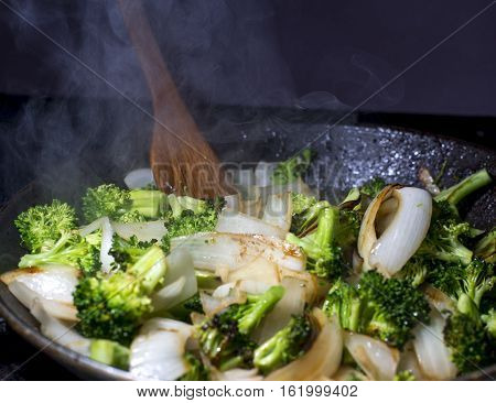 Broccolie and onion stirfry being cooked in pan