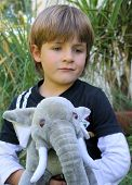 Portrait of a little boy playing with his toy elephant in the garden poster