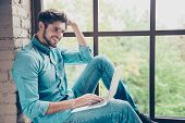 Happy smiling man sitting on windowsill and typing on laptop poster