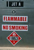 Jet A fuel pumps and storage tanks at an airport with the no smoking and flammable warnings poster