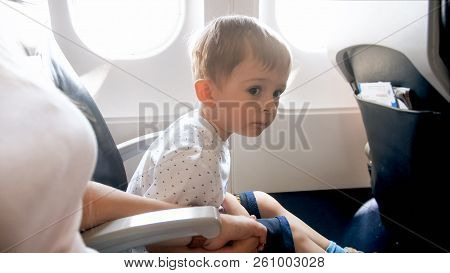 Little Toddler Boy Holding By Hand His Mother During First Flight In Airplane