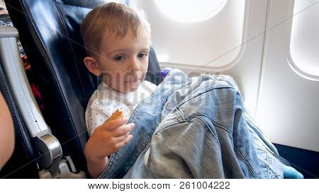 Portrait Of Cute Little Boy Covering In Jascket Sitting In Airplane Passenger Seat