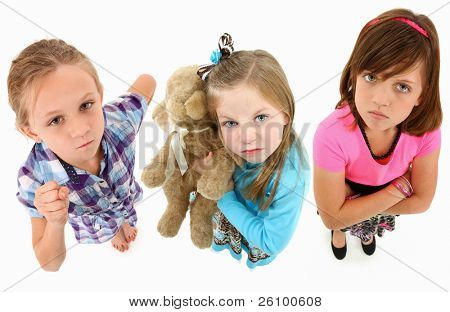 Adorable group of angry 7 year old girls over white background looking up towards camera.  Top view over white background.