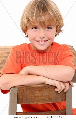 Attractive 8 year old boy in elementary school desk over white background.
