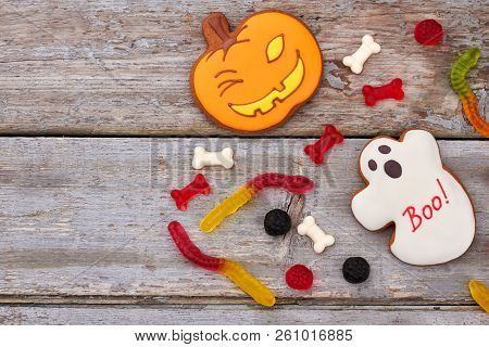 Halloween Sweets On Wooden Background. Halloween Cookies And Jelly Candies, Copy Space. Happy Hallow