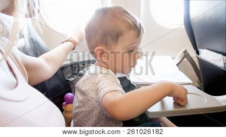2 Years Old Toddler Boy Flying With Beautiful Young Mother In Airplane
