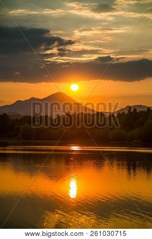 A Beautiful, Colorful Sunset Landscape With Lake, Mountain And Forest. Natural Evening Scenery Over