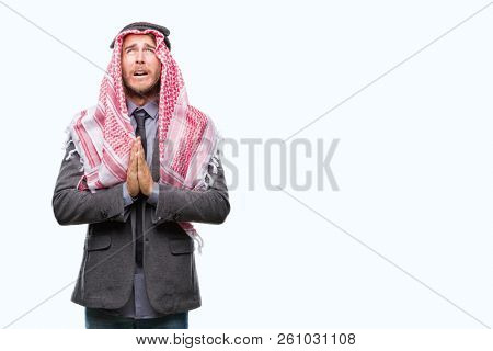 Young handsome arabian man with long hair wearing keffiyeh over isolated background begging and praying with hands together with hope expression on face very emotional and worried. Asking for forgiven
