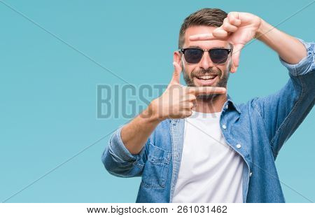 Young handsome man wearing sunglasses over isolated background smiling making frame with hands and fingers with happy face. Creativity and photography concept.