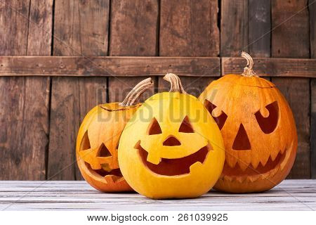 Traditional Halloween Pumpkins On Wooden Background. Funny And Scary Faces Of Pumpkins For Halloween