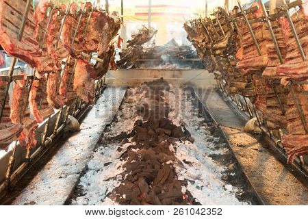 Asado, Traditional Barbecue Dish In Argentina, Roasted Meat Of Beef Cooked On A Vertical Grills Plac