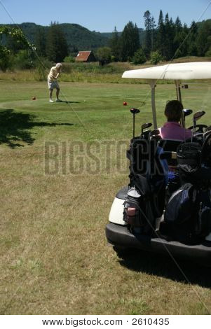 Woman In Golf Cart And Woman Teeing Off