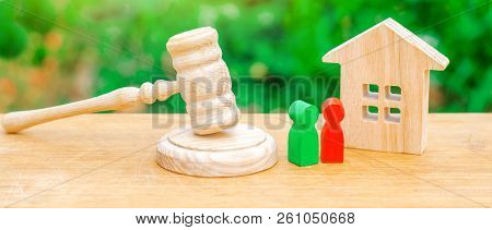 Wooden Apartment House With Keys And A Judge Hammer On A Green Background. The Concept Of The Trial